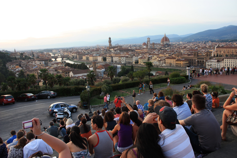 The Crowd at Piazzale Michelangiolo- A parking lot with a beautiful view of the city where many gather around sunset.